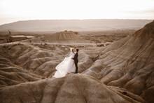 Newlyweds Embracing Near Rock At Sunset