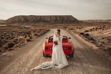 Excited Bride Standing Near Car In Desert
