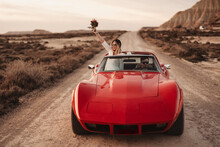 Newlyweds Travelling Through Desert In Red Car