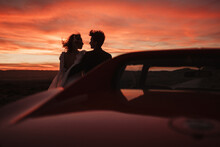 Loving Couple Resting Near Car At Sunset