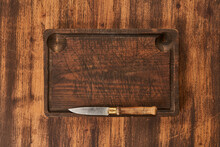 Cutting Board With Knife On Wooden Table