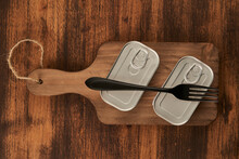 Cutting Board With Sealed Cans And Fork On Wooden Table