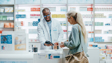 Pharmacy Drugstore Checkout Counter: Professional Black Pharmacist Sells Medicine To Diverse Group Of Multi-Ethnic Customers, They Pay Using Contactless Payment Credit Card To Buy Drugs, Vitamins