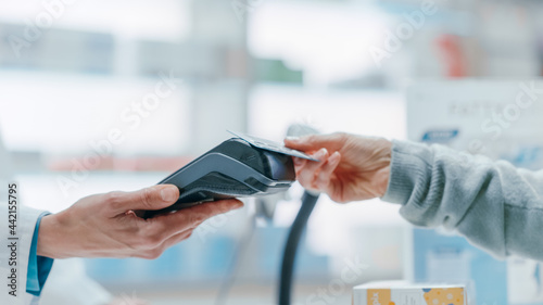 Fotografie, Obraz Pharmacy Drugstore Checkout Cashier Counter: Pharmacist and a Customer Using Contactless Credit Card with Payment Terminal to Buy Prescription Medicine, Health Care Goods