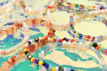 Closeup Of Necklaces And Bracelets Made From Colorful Beads And Pearls On A Turquoise Holographic Background.