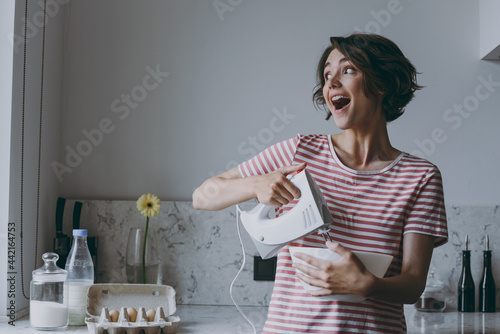Fototapeta Young excited brunette housewife woman 20s wearing casual clothes striped t-shirt using mixer whips yolks beats eggs cooking food in light kitchen at home alone