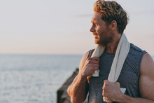 Close Up Young Strong Sporty Athletic Toned Fit Sportsman Man 20s In Sports Clothes Towel Warm Up Training Look Aside At Sunrise Sun Dawn Over Sea Beach Outdoor On Pier Seaside In Summer Day Morning