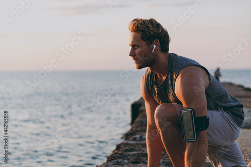 Fotografie, Obraz Young side view sporty toned fit sportsman man in sport clothes earphones mobile cell phone warm up train start sprint at sunrise sun dawn over sea beach outdoor on pier seaside in summer day morning