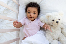 Happy Smiling African American Baby In A Crib With A Teddy Bear Falls Asleep Or Goes To Bed