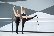 Side View Of Adult Female Instructor Helping Young Girl In Black Sportswear Learn Choreographic Move While Holding Handrails In Hall. Two Female Dancers Practicing, Ti Tech Interior. Sport Concept.