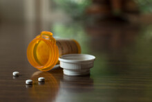Bottle Of Prescription Pills In An Orange Plastic Bottle With White Lid; Three Small White Pills Lay On Table With Out Of Focus Dinging Room In Background