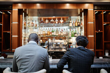 Back View Portrait Of Two Successful Business People At Bar In Hotel Lobby During Business Trip