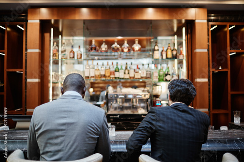 Tela Back view portrait of two successful business people at bar in hotel lobby durin
