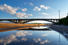 The Sky And The Communal Bridge Are Reflected In A Rain Puddle. Urban Landscape Of The City Of Krasnoyarsk On A Summer Day. City Embankment Of The Yenisei River