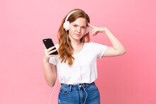 Pretty Red Head Woman Feeling Confused And Puzzled, Showing You Are Insane With Headphones And Smartphone