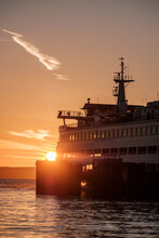 A Sunset With Orange Sky And The Silhouette Of A Ferry Boat