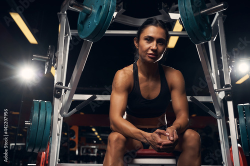 Tela Muscled young lady resting near a smith machine at the gym
