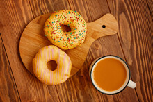 Flat Lay Of The Autumn Composition. A Mug Of Carrot Juice And Two Sweet Doughnuts With Yellow Glaze, Pink Stripes And Sprinkles. Breakfast On A Wooden Background.