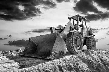 A stopping yellow excavator at beautiful sunset. Black and white