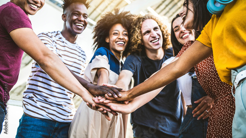 Leinwand Poster Multiracial happy young people stacking hands outside - Diverse friends unity to