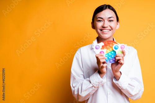 Obraz na plátně Cheerful smiling asian girl holding children's toys rainbow pop it and simple di