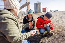 Grandmother Showing Chicken Eggs To Grandchildren On Sunny Farm
