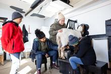 Family Milking Goat In Barn