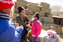 Mother Helping Daughter Blow Nose At Hay Bales On Sunny Farm