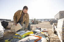 Worker Looking At Bag Of Cement In Industrial Yard