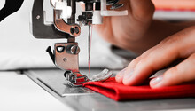 Woman's Hands With Red Fabrics At Sewing Machine. Self Made Clothes Concept.Hobby Concept. Clothes Repairing Concept.