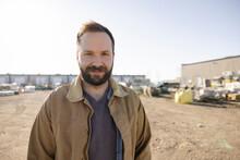 Portrait Of Cheerful Worker In Industrial Yard