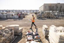Worker Walking Past Building Materials In Industrial Yard
