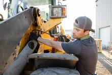 Worker Repairing Forklift In Industrial Yard