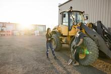 Colleagues Talking Beside Forklift In Industrial Yard