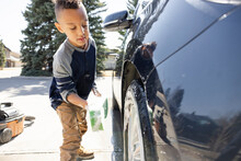 Boy Cleaning Car Tire Rim With Foamy Sponge In Driveway