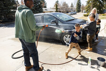 Father Spraying Water At Son, Family Washing Car In Driveway