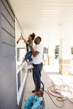 Father And Daughter Cleaning Windows On Front Porch