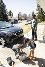 Father And Children Washing Car In Driveway