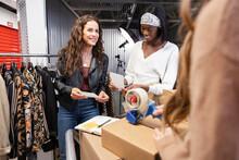 Female Clothing Entrepreneurs Shipping Boxes In Storage Facility