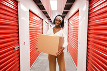 Portrait Happy Woman With Cardboard Box In Storage Facility Corridor