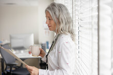 Female Doctor With Coffee Reviewing Medical Record In Clinic
