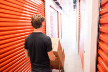 Young Man Pushing Hand Truck With Boxes In Storage Facility Corridor