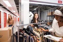 Female Fashion Entrepreneurs With Clothes Rack In Storage Facility