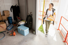 Woman Moving Garden Tools Into Storage Facility Locker