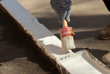 Paints The Kerb With White Paint. Brush With Paint For The Road Curb.