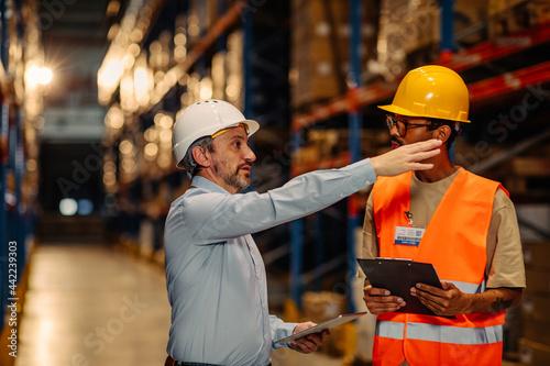 Warehouse staff meeting, worker with manger Fototapeta