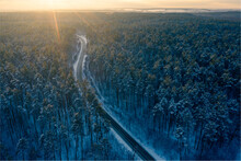 Aerial View Of A Winter Road With In The Middle Of A Snowy Forest At Sunset