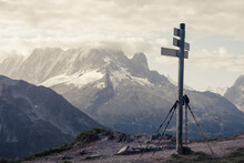 Hiking Poles Leaning On Signpost In Front Of Mountains