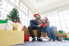 Asian Happy Family And Little Girl Celebrating At Christmas Pull The Paper Fireworks And Gift Box With Christmas Tree In Living Room. My Dad, Mom And Daughter In Santa Hats Sitting Couch At Home.