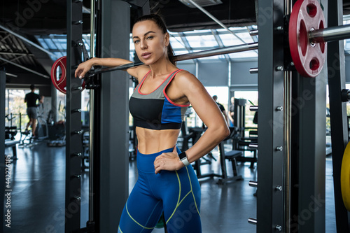 Tela Confident athletic girl standing near Smith machine at gym